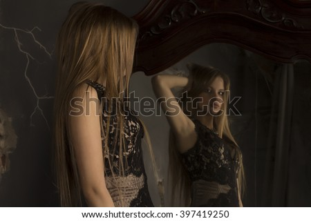 Attractive  woman looking herself reflection in mirror in the shadows - stock photo
