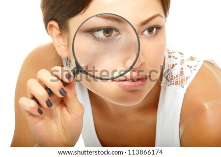 Attractive woman looking through a magnifying glass over white background - stock photo
