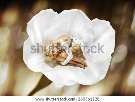 Attractive woman lying on a flower - stock photo
