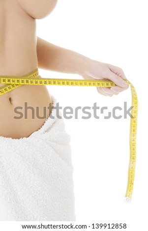 Attractive woman measuring her waist with tape - stock photo