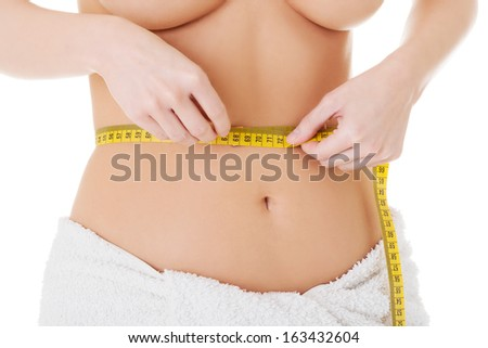 Attractive woman measuring her waist with tape over white background.  - stock photo