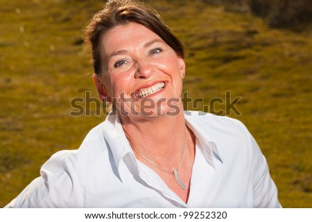 Attractive woman middle aged enjoying outdoors. Clear sunny spring day with blue sky. - stock photo