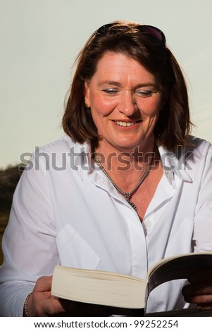 Attractive woman middle aged reading a book and enjoying outdoors. Clear sunny spring day with blue sky. - stock photo