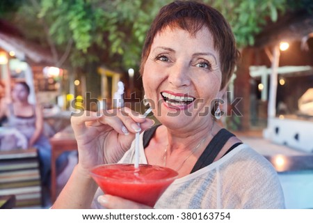 attractive woman of 50 years with a cocktail in hand, in a cafe - stock photo