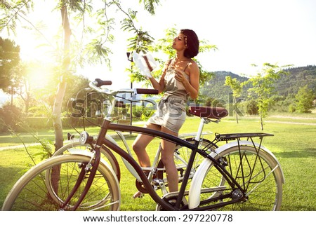 attractive woman on a bicycle resting under a tree - stock photo