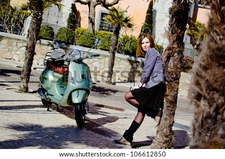 Attractive woman on a  retro scooter - stock photo