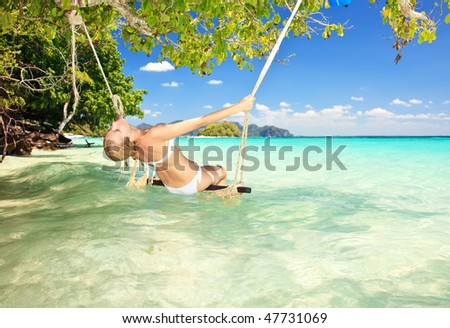 attractive woman on a swing in paradise - stock photo