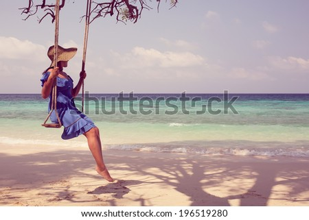 attractive woman on a swing in paradise in a straw hat and blue dress against the sky, palm trees. vintage - stock photo