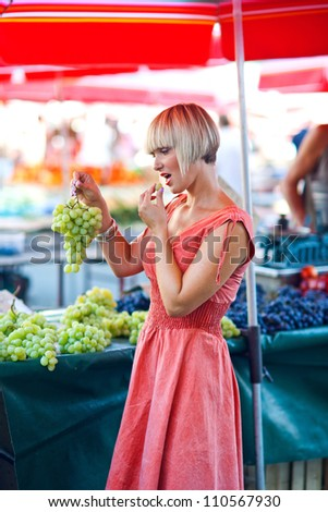 attractive woman on city market tasting grapes and choosing fruit - stock photo