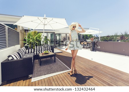 Attractive woman on luxurious penthouse balcony - stock photo