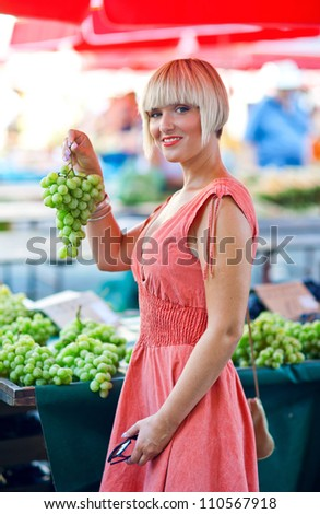 attractive woman on market with grapes - stock photo