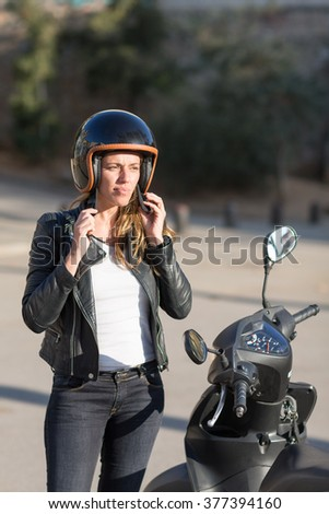Attractive woman on motor bike takes off her helmet - stock photo