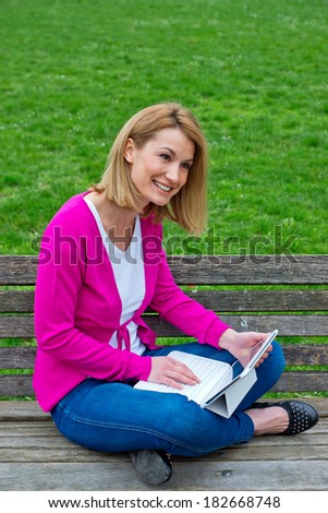 attractive woman on the park bench with laptop computer