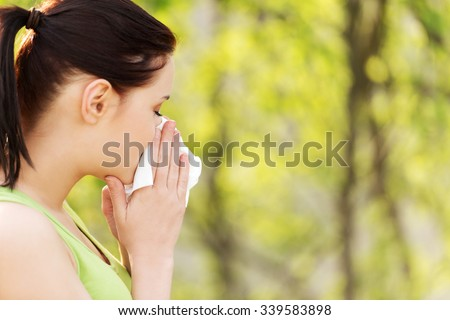 Attractive woman outdoor with tissue having allergy. - stock photo