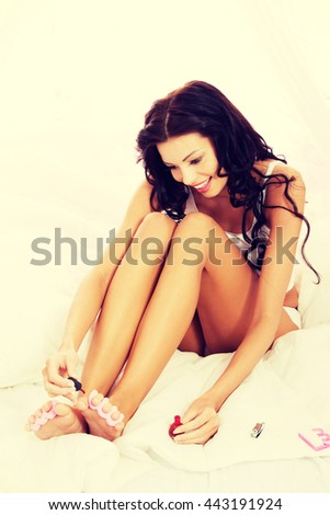 Attractive woman painting her toes. - stock photo
