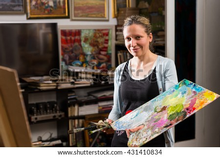 Attractive woman painting in a studio holding a colorful artists palette and paintbrush in her hand as she assesses her canvas standing on an easel - stock photo