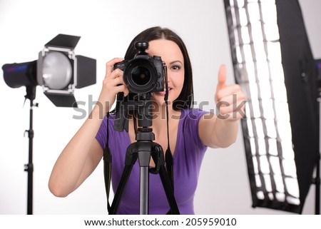 Attractive woman photographer at work in his studio - stock photo