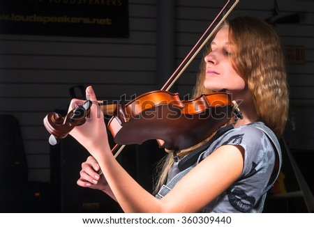 Attractive woman plays on violin - stock photo