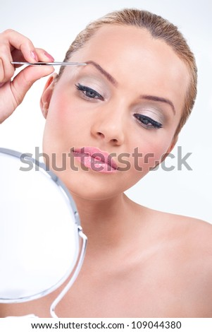 Attractive woman plucking her eyebrows and looking in mirror - stock photo