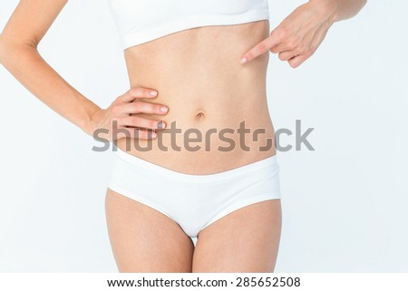 Attractive woman pointing her belly on white background