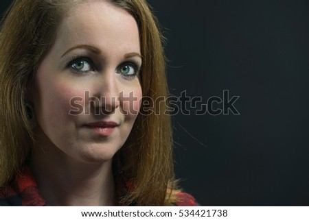Attractive woman portrait against a black backdrop in a studio.