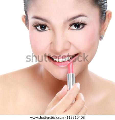 attractive woman portrait on white background applying lipstick - stock photo