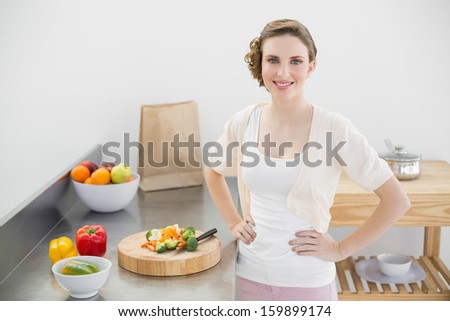 Attractive woman posing in her kitchen with hands on hips smiling at camera