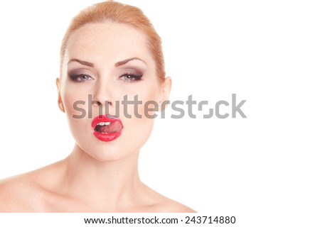Attractive woman posing in studio, showing tongue closeup over white. Wearing smoky eye and red lips. Looking at camera. Isolated  - stock photo