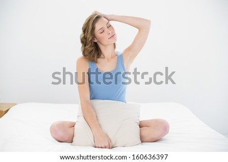 Attractive woman posing sitting on her bed holding a pillow with eyes closed