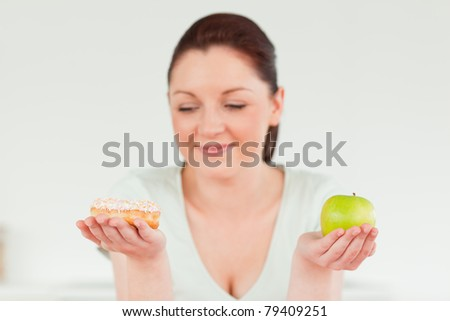 Attractive woman posing while holding a donut and a green apple against a white background