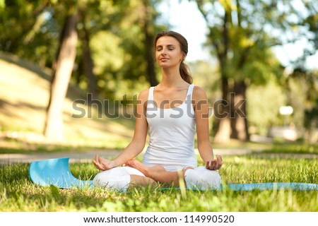 Attractive woman practices yoga in nature. Lotus Pose, eyes closed - stock photo