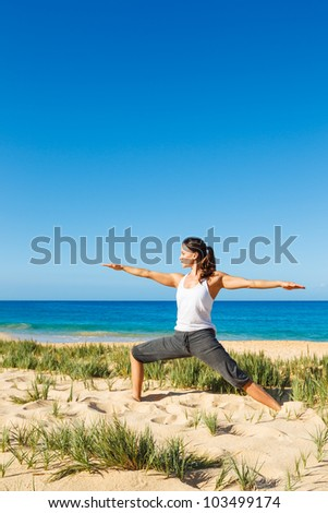 attractive woman practicing yoga at the beach
