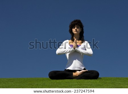 Attractive woman practicing yoga outdoors. Grain added - stock photo