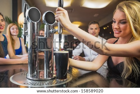 Attractive woman pulling a pint of stout in front of her friends in a restaurant - stock photo