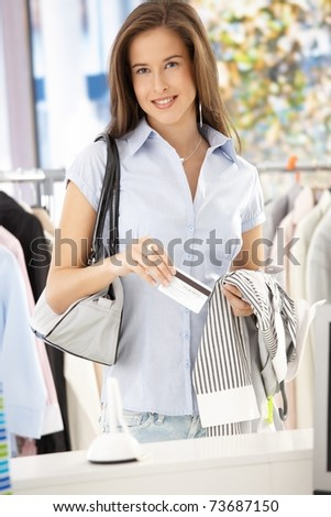 Attractive woman purchasing shirt in clothes store with credit card, smiling at camera.?