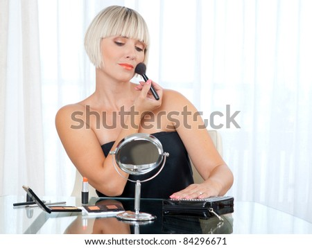 attractive woman putting make up in her home
