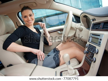 attractive woman putting on safety belt in her car - stock photo