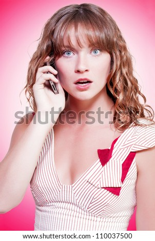 Attractive woman reacting with astonishment and disbelief to news on her mobile phone on a pink studio background with colour gradient - stock photo