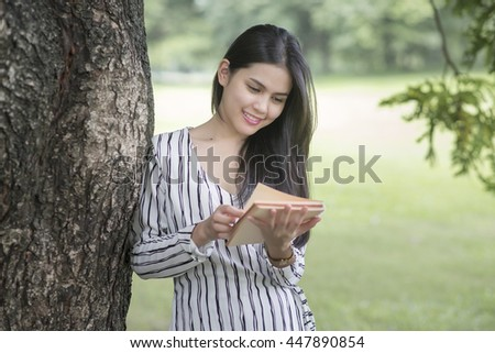 Attractive woman reading a book in the park