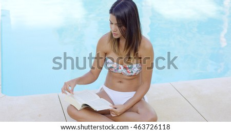 Attractive woman reading a book poolside