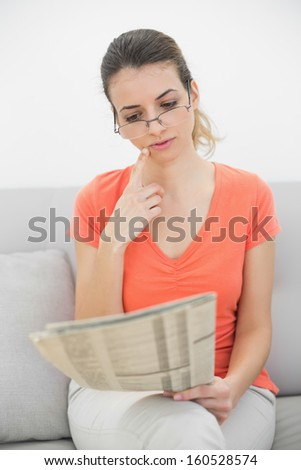 Attractive woman reading a magazine sitting on couch in the living room