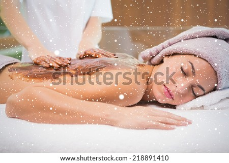 Attractive woman receiving chocolate back mask at spa center against snow falling