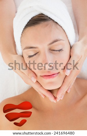 Attractive woman receiving facial massage at spa center against heart - stock photo