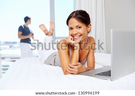 attractive woman relaxes at home using laptop computer while husband drinks coffee. leisure couple