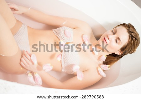 Attractive woman relaxing in bath with rose petals  - stock photo