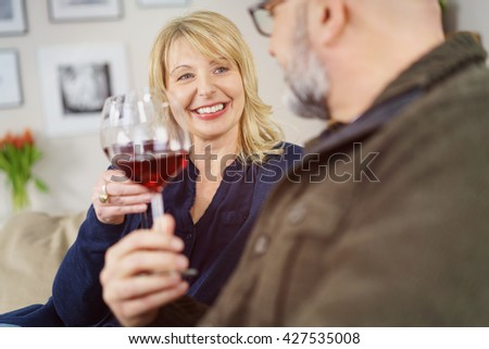 Attractive woman relaxing with her husband at home sitting on the sofa chatting and drinking red wine - stock photo