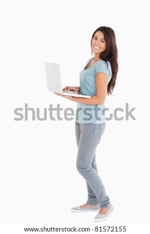 Attractive woman relaxing with her laptop while standing against a white background - stock photo