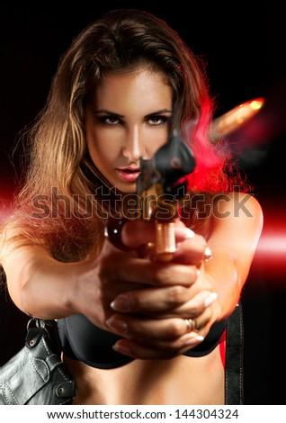 Attractive woman shooting from golden gun in studio - stock photo
