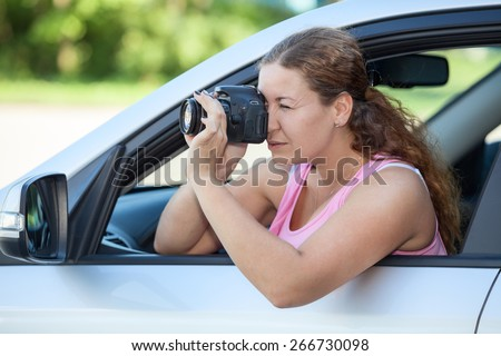 Attractive woman shooting with dslr camera while sitting inside on car - stock photo