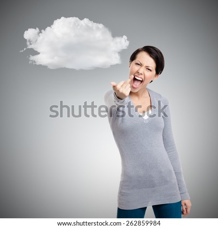 Attractive woman shows a vulgar, obscene finger gesture, isolated on grey background - stock photo